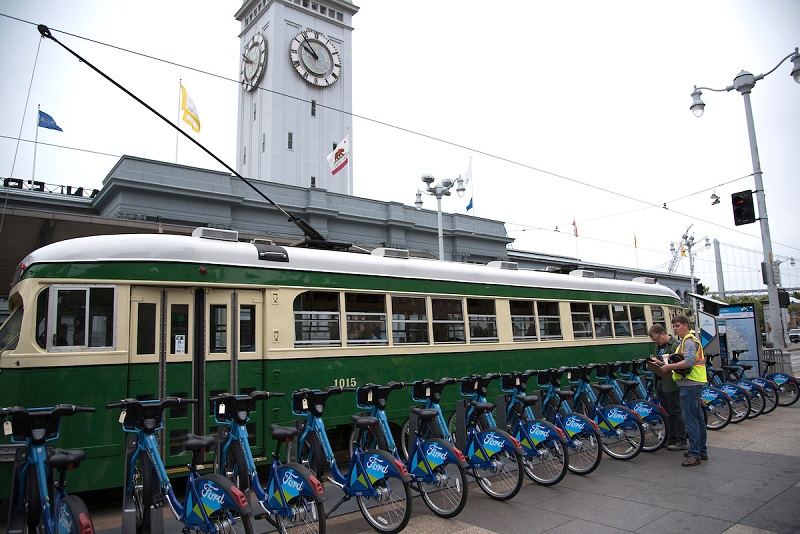 A Ford GoBike bike-share station in front of the Ferry Building on The Embarcadero, with a Muni streetcar passing behind.