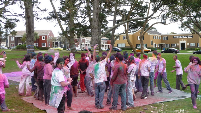 Dozens of people covers in colorful dye in the middle of a park surrounded by trees