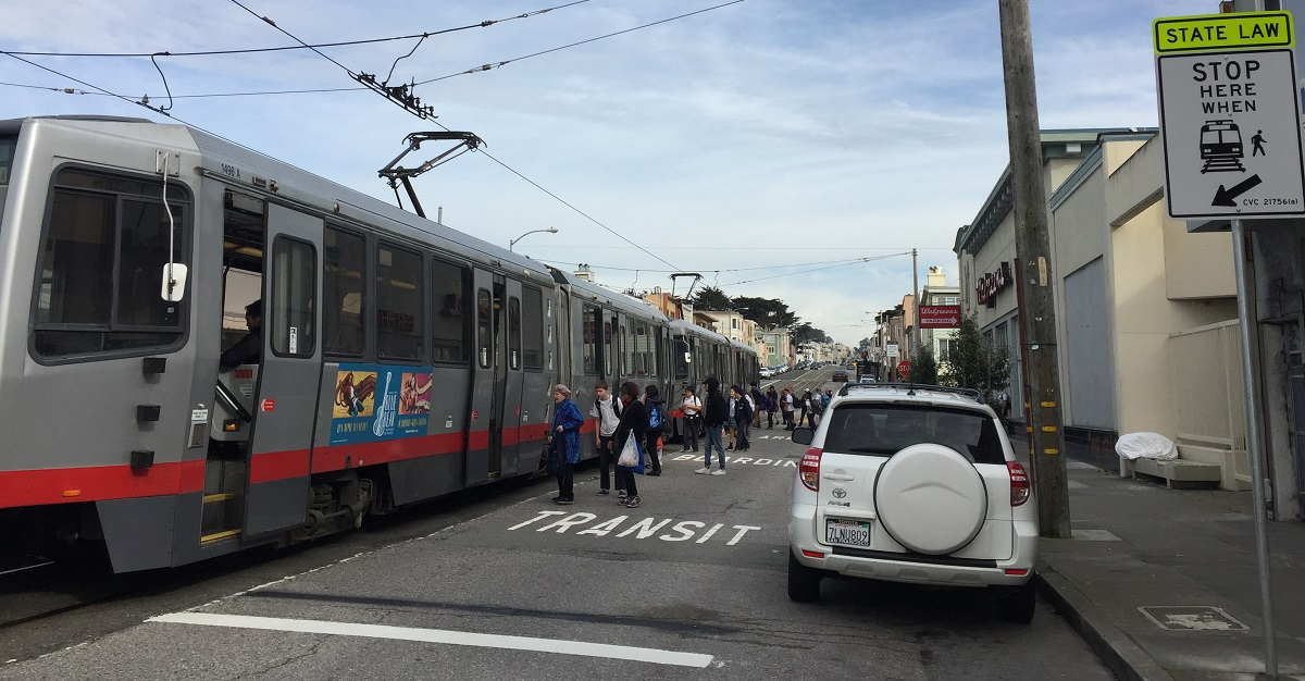 "People on Taraval Street board a stopped Muni train from the roadway with pavement markings that say, ""TRANSIT BOARDING ZONE"" and a posted sign that says, ""STATE LAW - STOP HERE WHEN"" along with an image of a train and passenger."