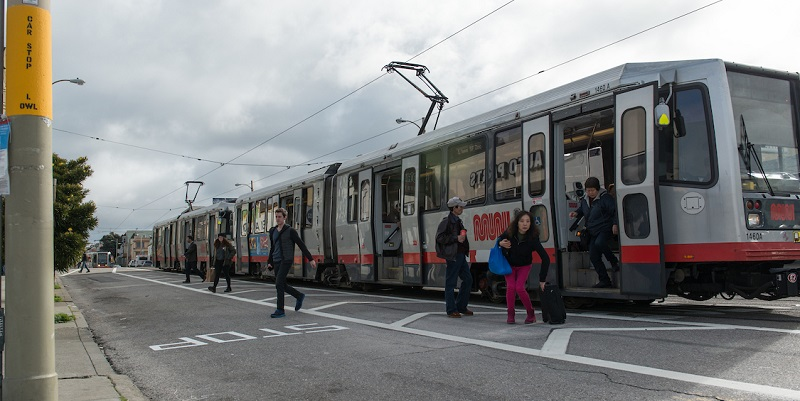 "People on Taraval Street alight from a stopped Muni train onto the roadway in a marked ""clear zone,"" an area striped between the train and the adjacent traffic lane."