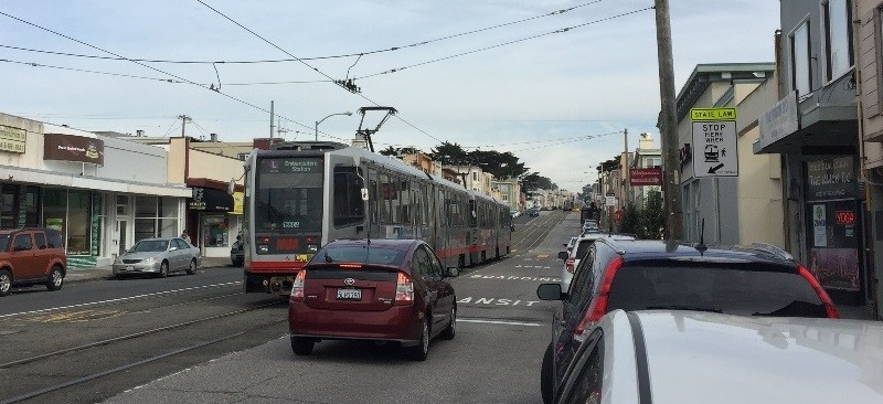 "A car on Taraval Street stopped behind a Muni train with its doors open next to an area of the roadway with pavement markings that say, ""TRANSIT BOARDING ZONE."""