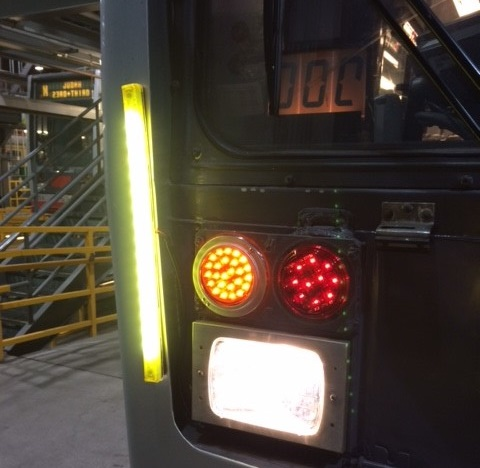 The end of a Muni train with a long vertical, yellow light activated on its side edge.