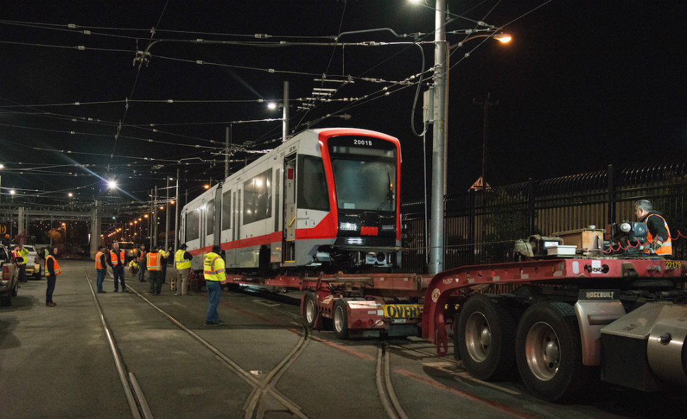 Crews offloading the new Muni train from a truck bed at night.