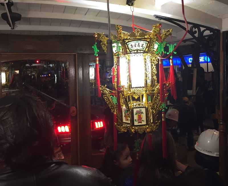 An ornate gold, red and green lantern shines inside a motorized cable car.