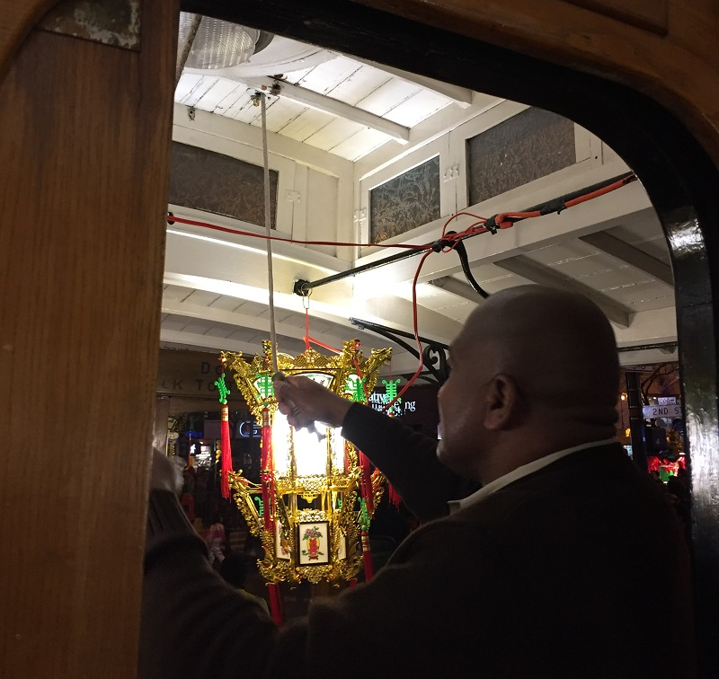 Leonard Oats rings the cable car bell as the rubber-tire cable car makes its way through the Chinese New Year Parade.