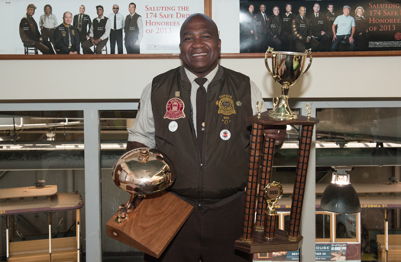 2016 World Champion Cable Car Bell Ringer Leonard Oats standing and holding trophies.