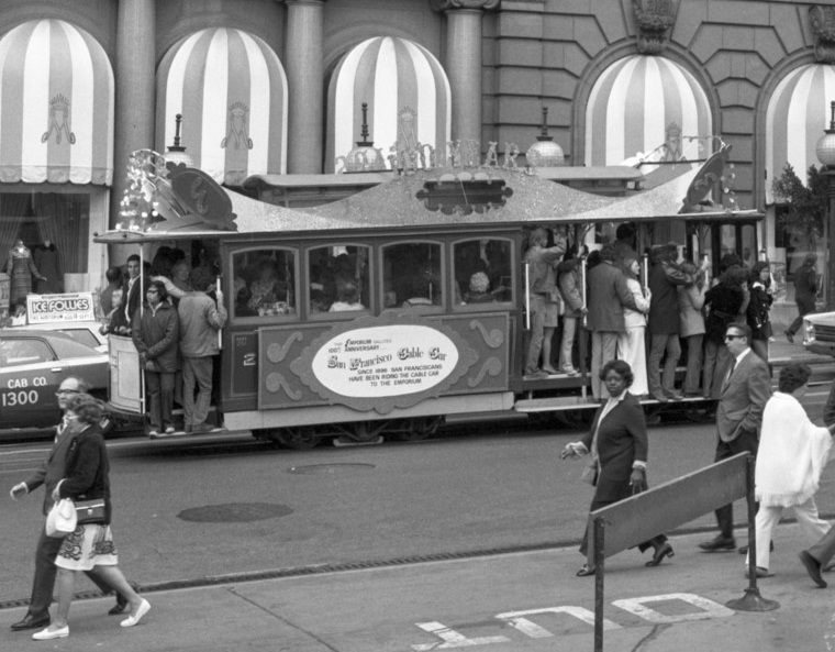 Black and white photo from august 1973, a side view of cable car 23 on Powell Street in front of the St. FRancis Hotel.  The car is covered with decorative, sparkling panels to celebrate the 100th anniversary of the cable car system.