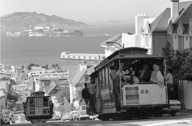 Black and white photograph taken in august of 1973 showing Cable Car 23 descending the Hyde Street hill from Chestnut Street. San Francisco Bay and Alcatraz island can be seen in the background.