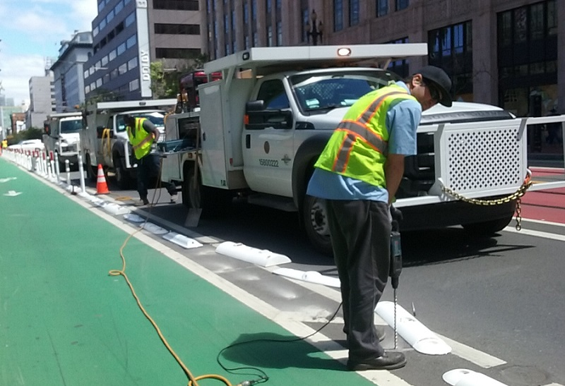 Along the edge of the bike lane on Market Street, a uniformed SFMTA crew member holds a long drill pointed into the ground to install safe-hit posts.