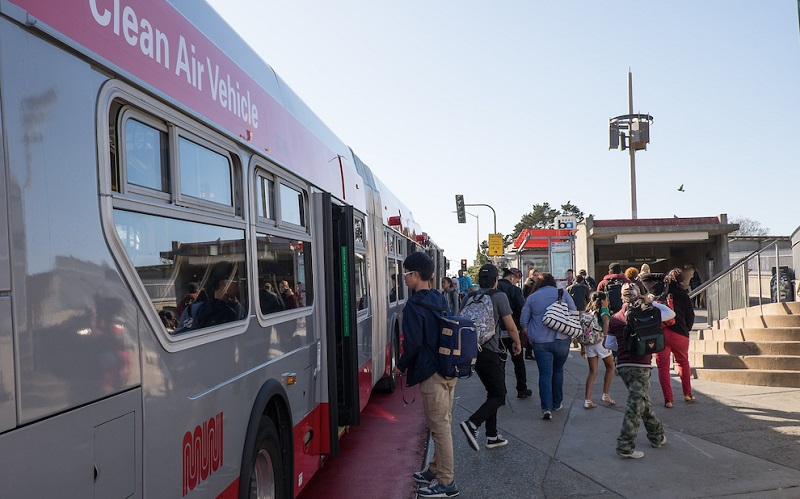 People board a Muni bus in front of Balboa Park Station.