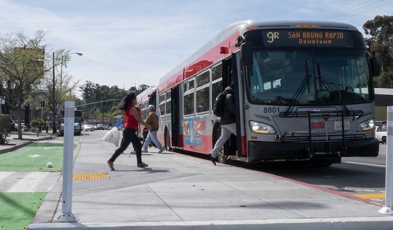 People board a Muni bus at a stop using a new bus boarding island, with a bike lane placed between the island and the sidewalk, on the 9R San Bruno Rapid route.
