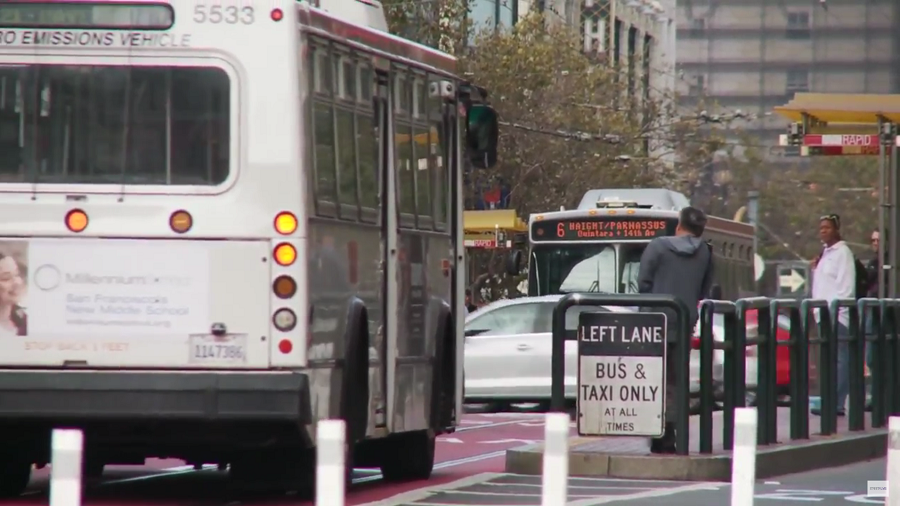 "Muni buses on Market Street travel down red-colored transit-only lanes, approaching riders waiting on a boarding island, with a bus shelter labeled, ""Muni Rapid."""