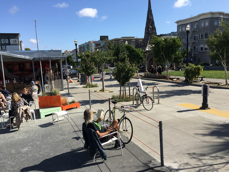 People sitting in chairs and bicycles parked in a public space next to Patricia's Green park on Octavia Street near Hayes Street.