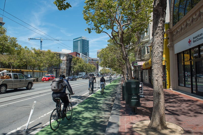 Bike lane at road-level, with green-painted pavement and plastic posts separating it from vehicle traffic.
