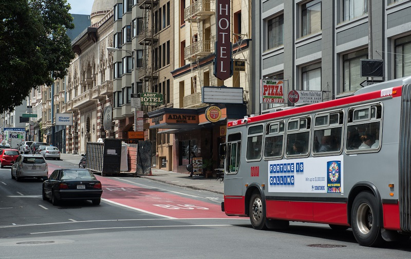 A Muni bus travels down a red transit-only lane on downtown Geary Street as cars travel in the adjacent traffic lanes.