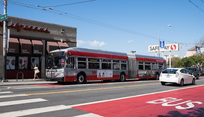 A Muni bus travels down a red transit-only lane on Mission Street at 30th Street as cars travel in the adjacent traffic lanes.