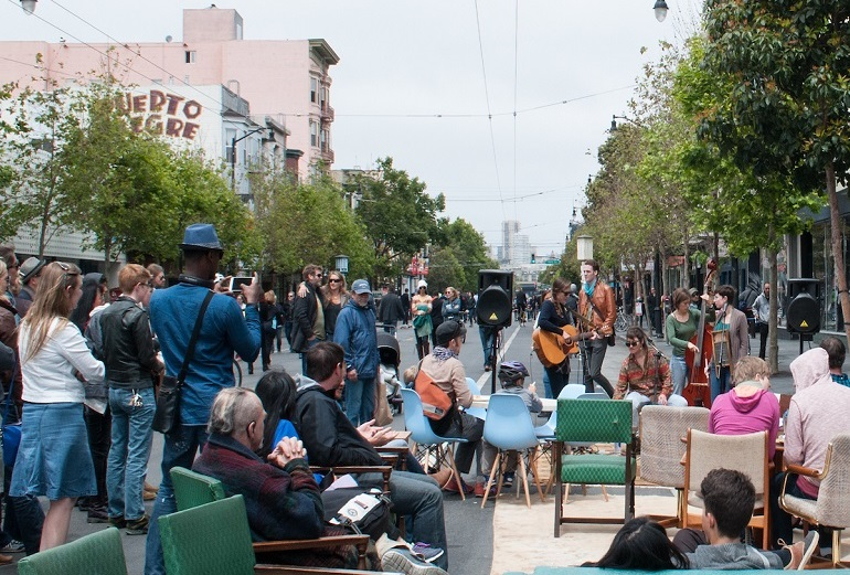 People watching a musical performance on a car-free roadway at Sunday Streets on Valencia Street.