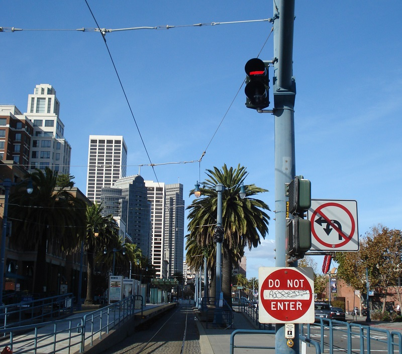 A traffic signal displaying a red, horizontal rectangle on a pole next to the Muni trackway on The Embarcadero.