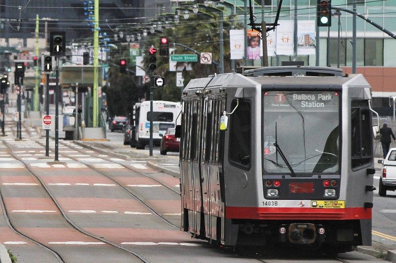A Muni train on 3rd Street approaches a set of traffic signals. Below a left turn signal is a small signal displaying a white image of a train.