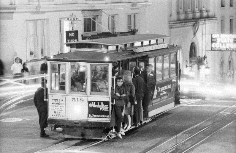 A 1968 photo of people riding a cable car at night as it stops at Powell and Bush streets.
