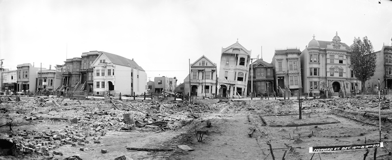 Black and white photo showing damaged houses, leaning and sinking into the ground on South Van Ness and 18th St, taken May 9, 1906 after great earthquake and fire.