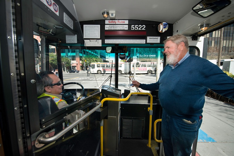 A Muni operator, seated in the bus driver seat, greets a customer with a smile.