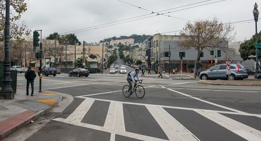 Daytime view looking west on 14th Street at its intersection with Market and Church streets with people walking, driving and a man bicycling.