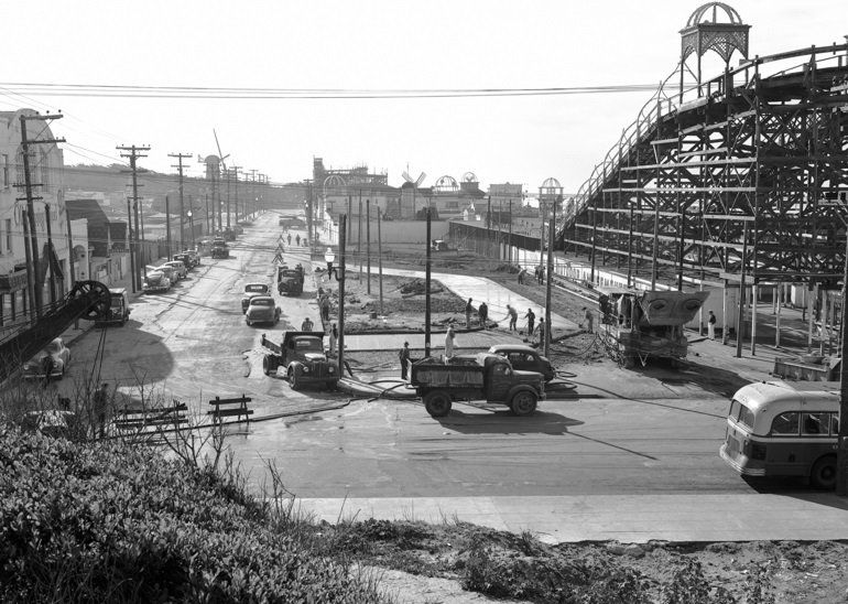 Black and white photograph looking south from Balboa and La Playa streets at construction of bus terminal in 1949.  To the right is a wooden amusement ride in Playland at the Beach amusement park.