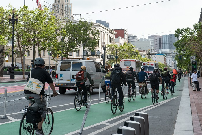Group of bicyclists in a protected bike lane going east on Market in the afternoon