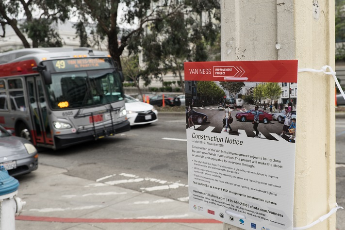 Bus driving up Van Ness Avenue, foreground is a construction notice posted for the Van Ness Improvement Project.