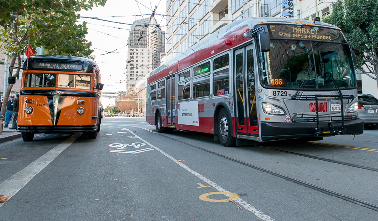 color photo showing two Muni buses next to each other on Steuart street.  On the left is a 1938 orange and black painted White brand bus and on the right is a new 2013 red and grey New Flyer bus.