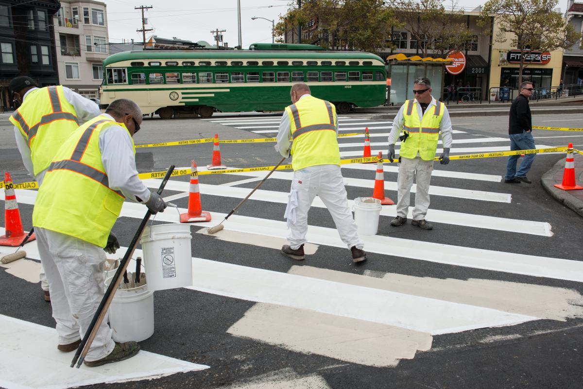 SFMTA workers painting pedestrian safety area