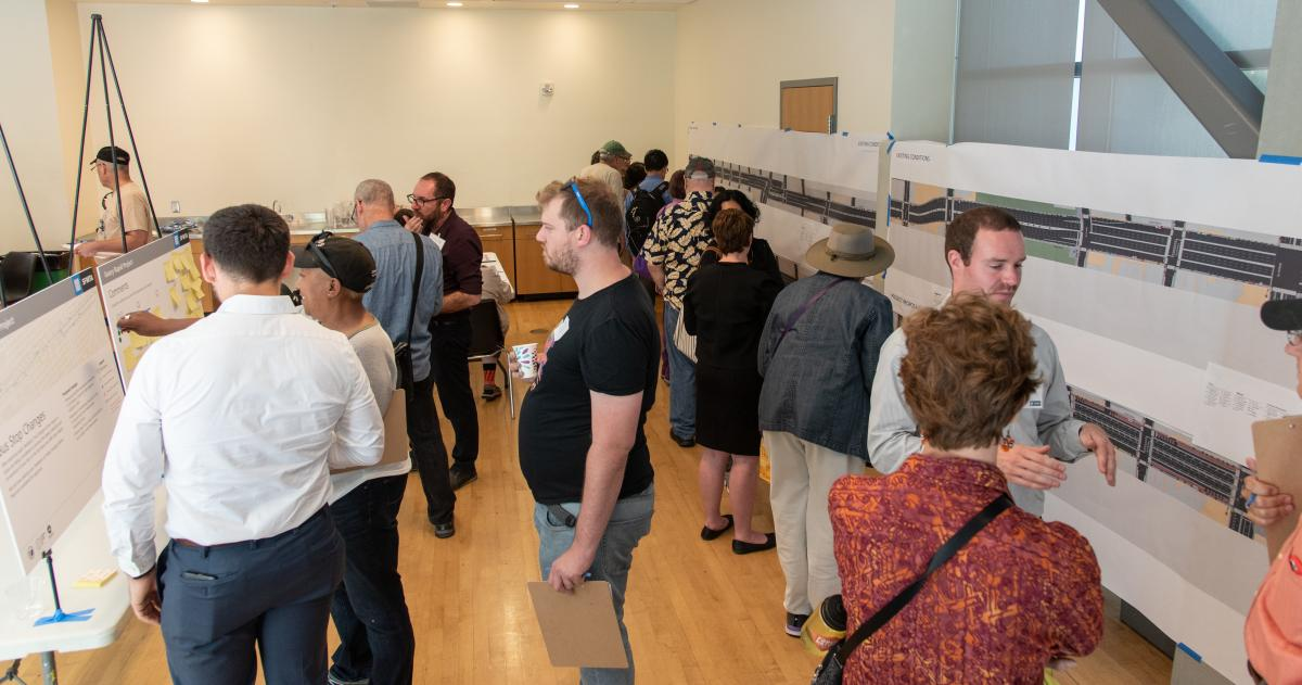 Image shows members of the public engaging with Geary Rapid Project staff at the project's Open House.