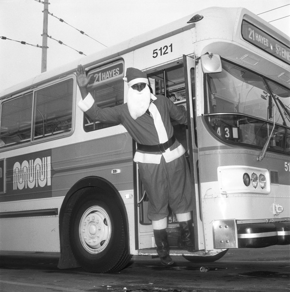 a person dressed as santa claus waves from a Muni bus