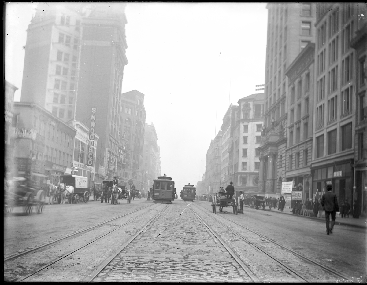 street scene with horse drawn carts, pedestrians, and cable cars