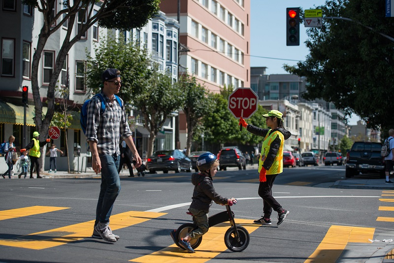A crossing guard helping a father and son cross the street.