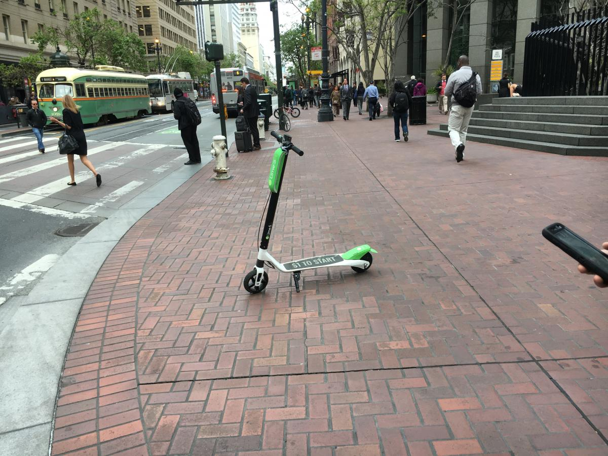 Lime scooter parked on the sidewalk on Market Street