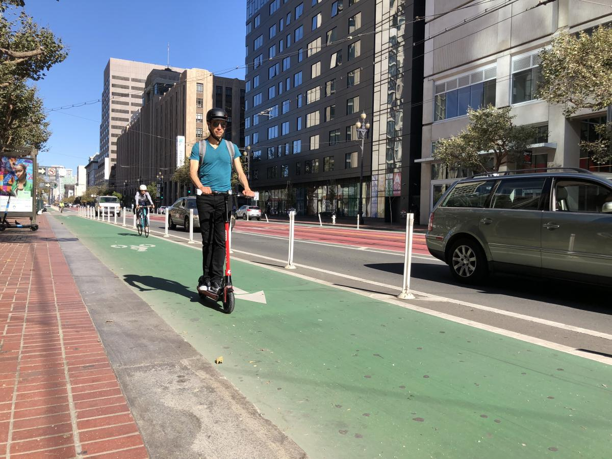 Man riding a scooter in a bike lane