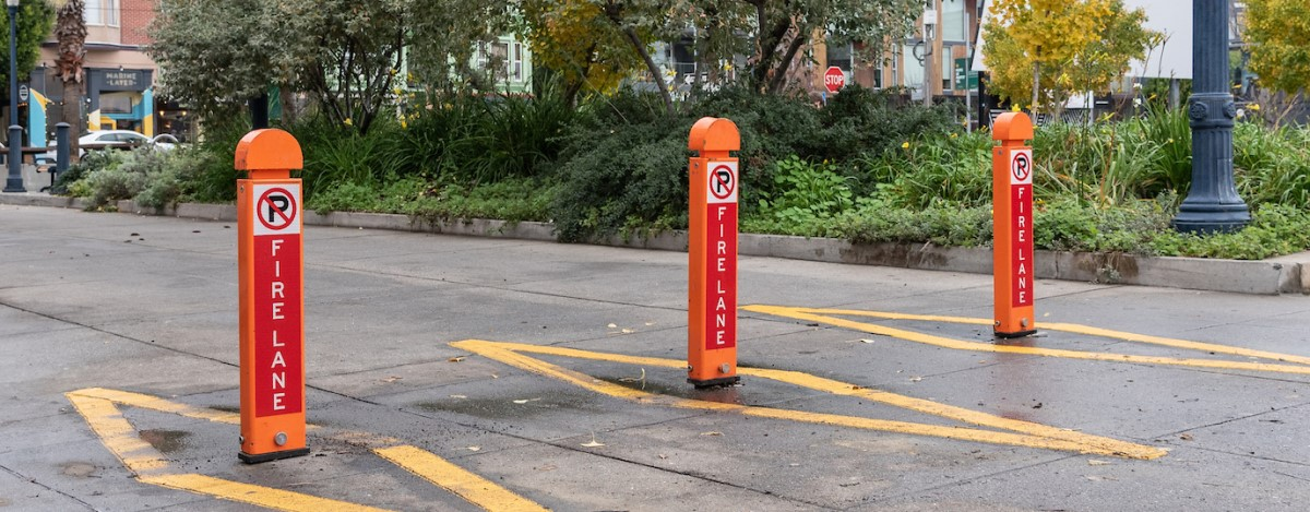 "three new collapsible ""bollards"" used to close street to cars"