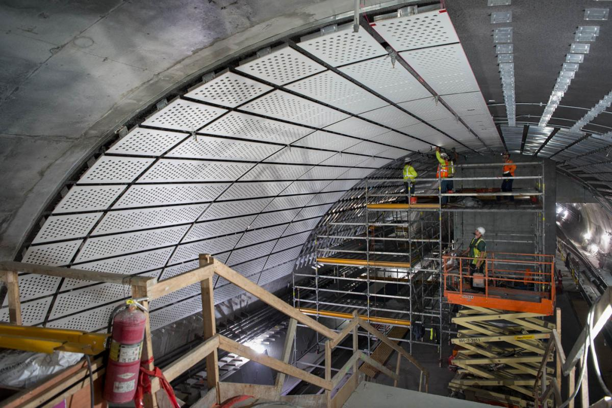 Sound reduction panels are being attached to steel brackets mounted to the arched concrete ceiling of the Chinatown-Rose Pak Station platform cavern.