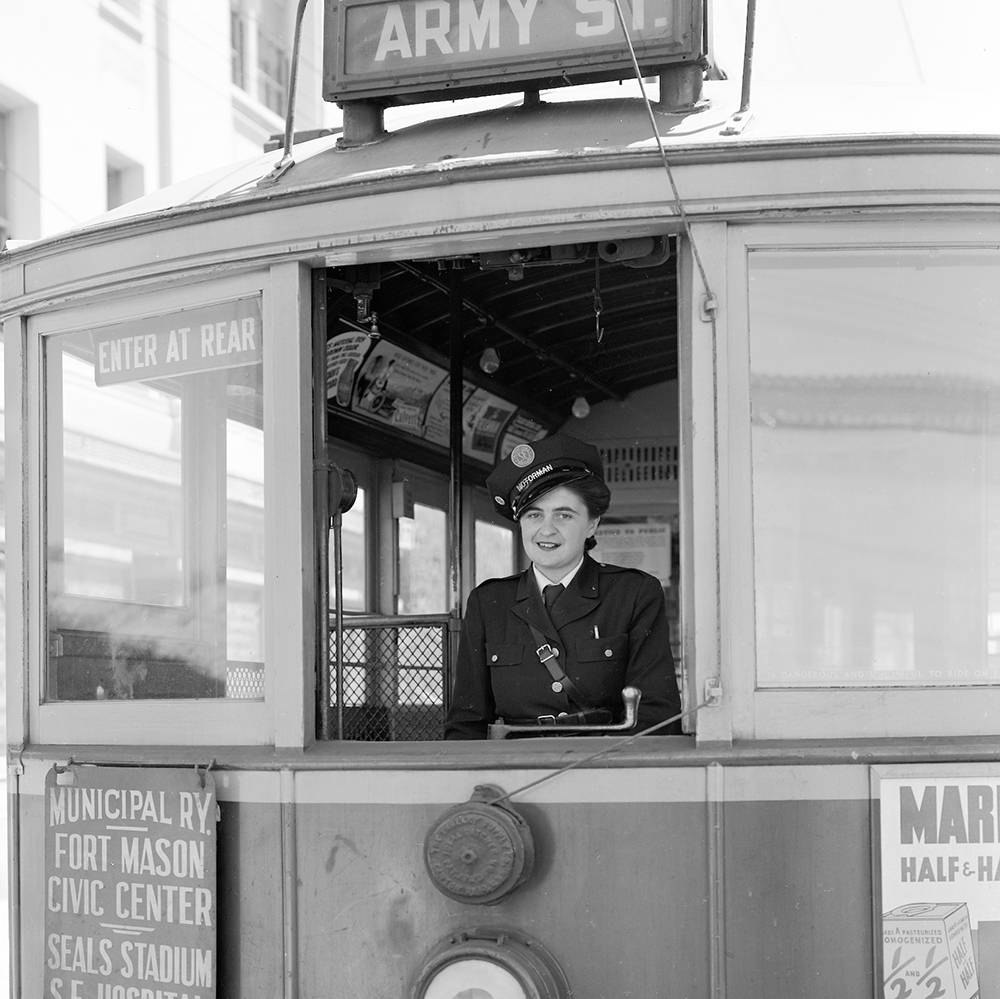 A woman wearing a muni uniform at the controls of a streetcar