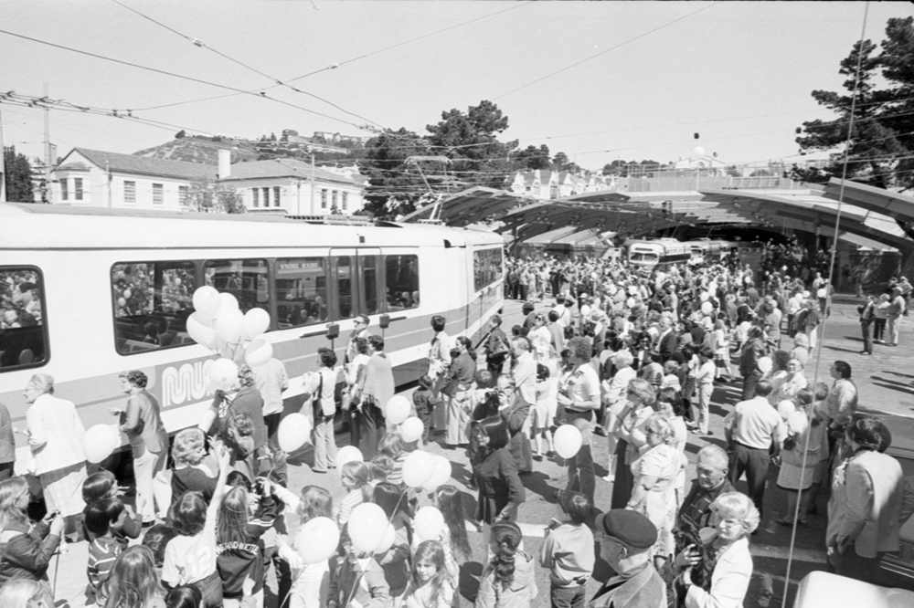 crowd of people with muni streetcars outside west portal station