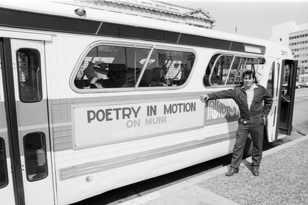 "person wearing muni uniform standing next to bus with ad reading ""poetry in motion on Muni, have a look!"" on side of bus"