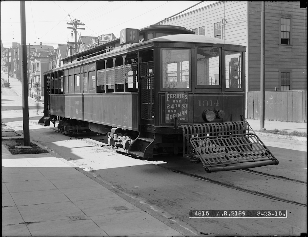 streetcar on street with houses in background