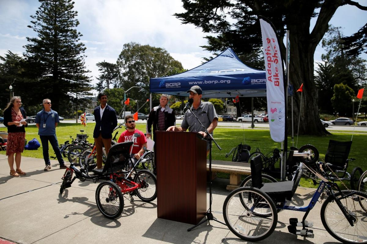 From left: Annette Williams of SFMTA, Lucas Tobin of SF Recreation and Parks, Neal Patel of Lyft, Kurt and Finn who are BORP participants, and Greg Milano of BORP stand in Golden Gate Park on a sunny day surrounded by different kinds of adaptive bikes. Greg, a white man in a baseball cap, stands a podium in front of a grassy area speaking into a microphone about the program.)""