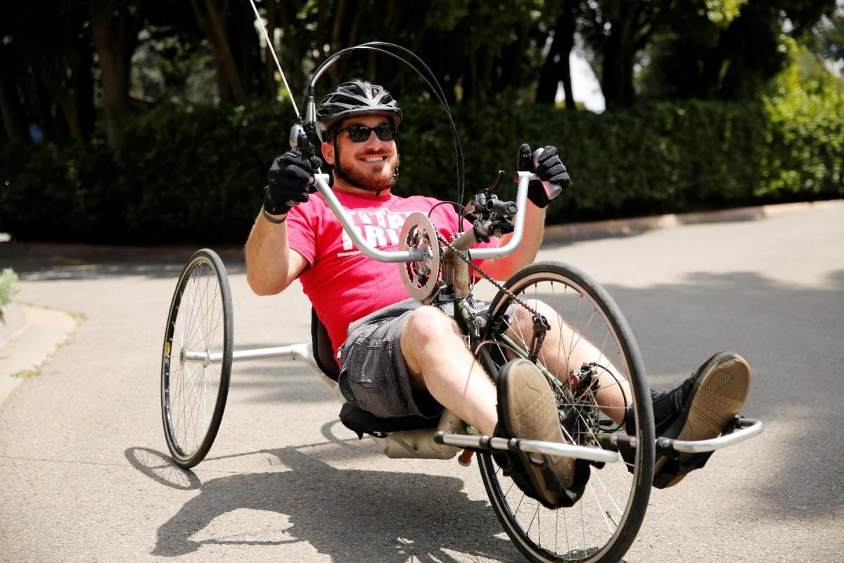 Kurt, a younger white man in a red T-shirt in sunglasses and a black cycle helmet, sits in a recumbent foot-pedal bike, holding the bike's handlebars and smiling.)
