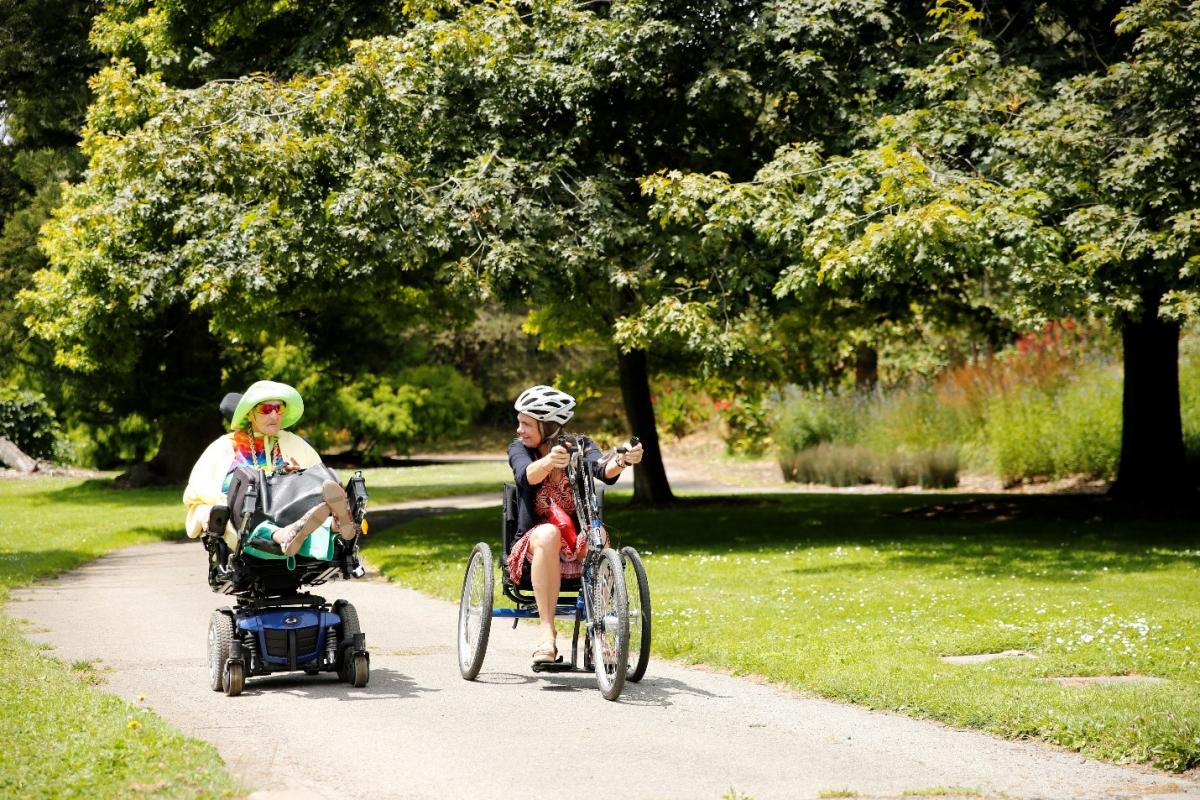 Sam Alicia, a member of the Paratransit Coordinating Council at SFMTA, and Annette Williams of SFMTA, move side-by-side down a paved pathway surrounded by trees and green grass on a sunny day. Sam Alicia uses her powered scooter, while Annette, in a helmet, uses the upright hand-pedal cycle.)