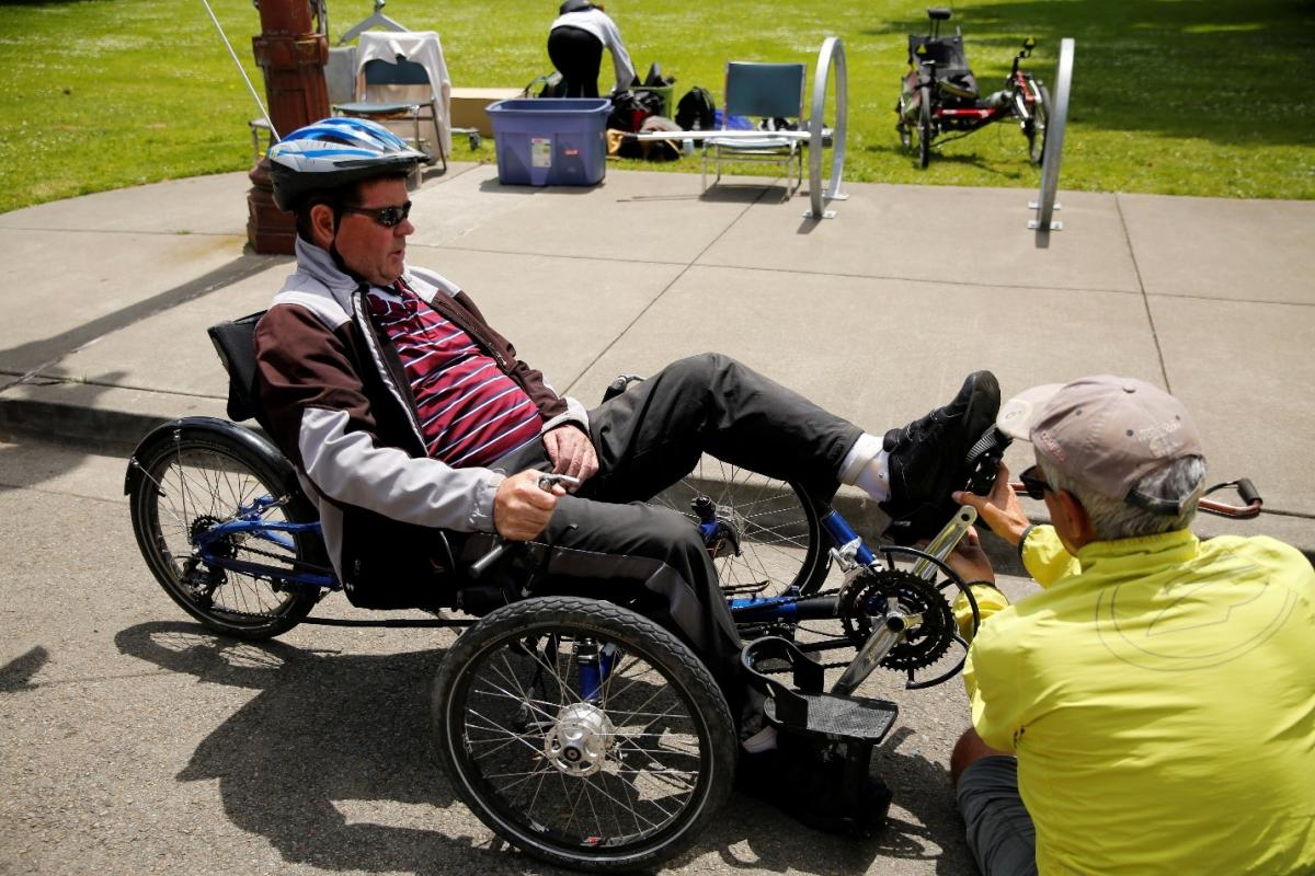 Finn, a BORP participant, is assisted by a BORP staff member and strapped into a recumbent trike. He is in sunglasses, a white and blue helmet, and a track jacket, while the BORP volunteer is in a yellow shirt and baseball cap with his back to the photographer.)