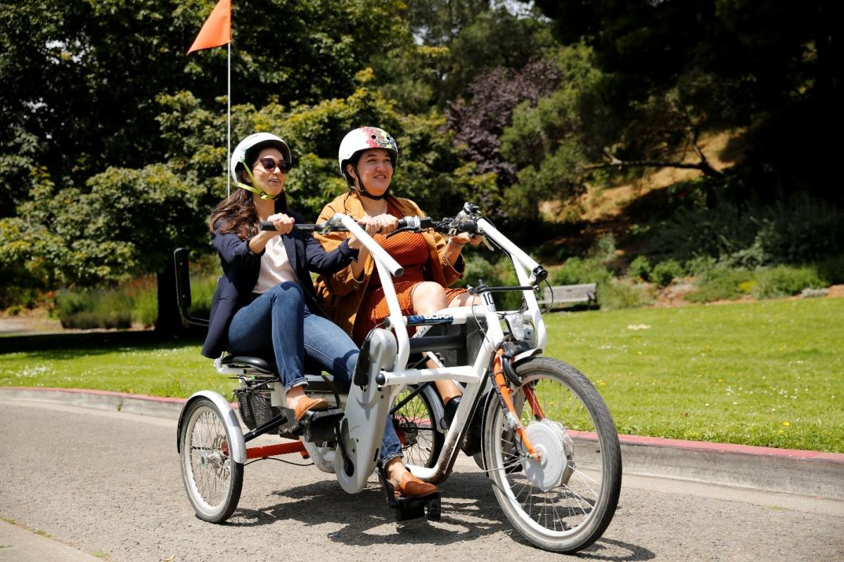 Erin McAuliff of SFMTA and Natasha Opfell of SF Paratransit, both younger women in blazers and bicycle helmets, sit side-by-side on the white, side-by-side tandem bike, moving down a paved road on a sunny day, with grass and trees in the background.)