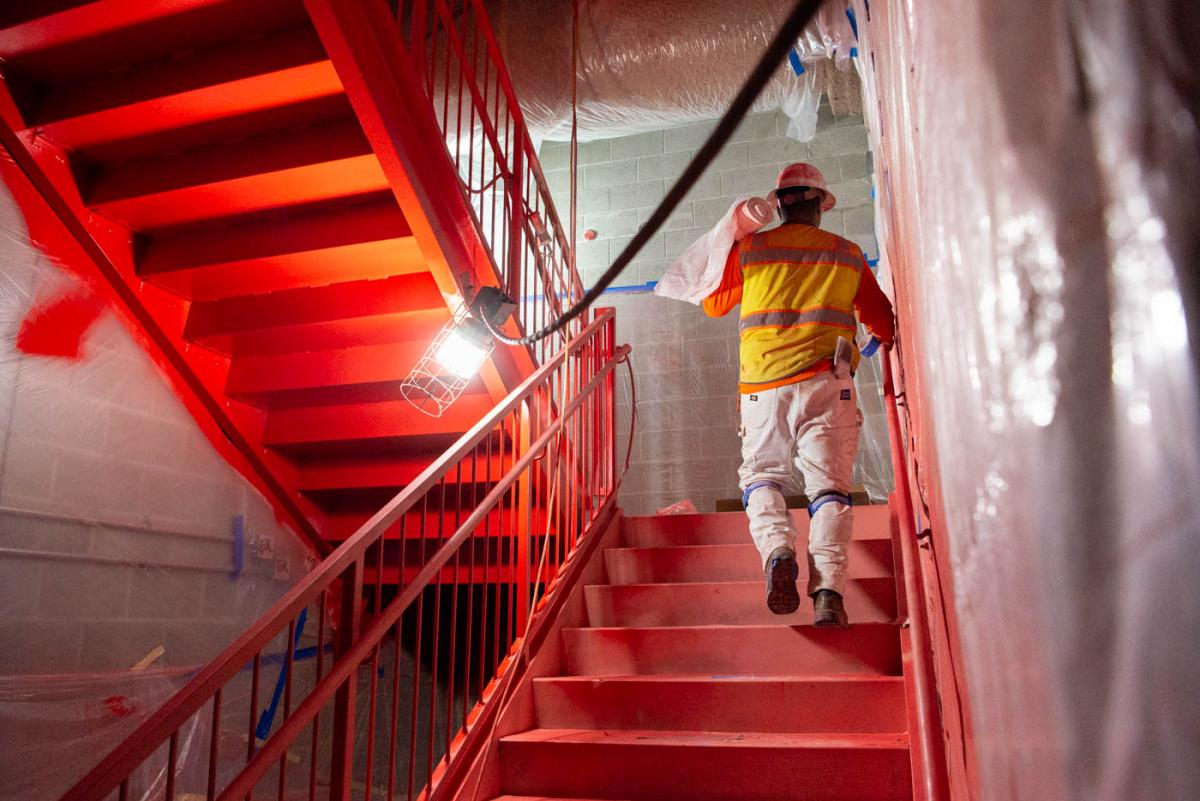 Emergency exit stairs at the north end of the station platform are being painted bright orange to aide in giving directions during an emergency.